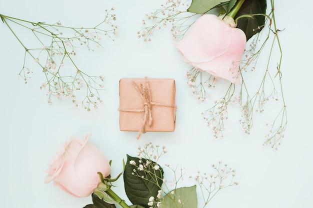 Una vista ambientale del contenitore di regalo spostato con i fiori su priorità bassa colorata blu