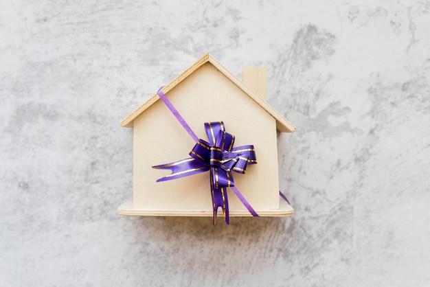 Una vista ambientale della casa di legno legata con l'arco del nastro viola sul muro di cemento