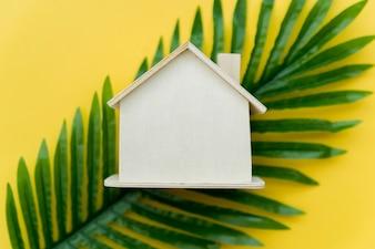 Una vista ambientale della casa di legno sopra le foglie verdi contro fondo giallo