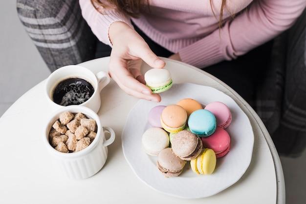 Una vista ambientale della donna che tiene maccherone con la tazza dei cubi dello zucchero bruno e caffè sulla tavola bianca