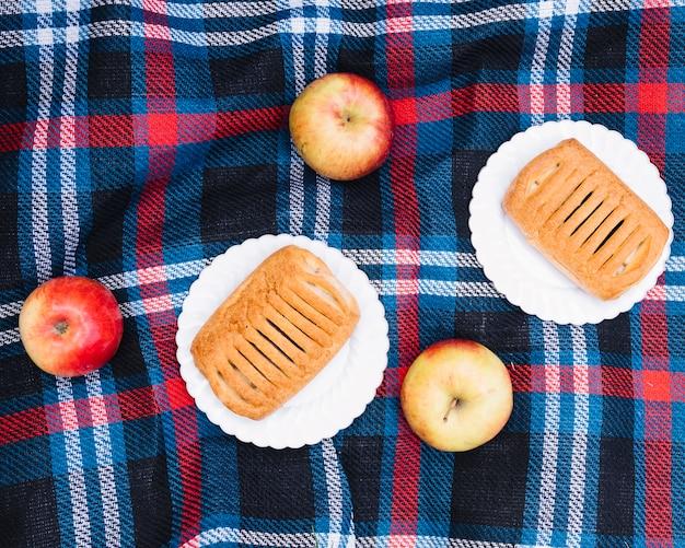 Una vista ambientale della pasta sfoglia sul piatto bianco con le mele rosse sopra la coperta