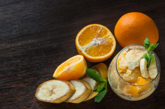 Una vista ambientale di arance e banana in vetro su fondo strutturato di legno