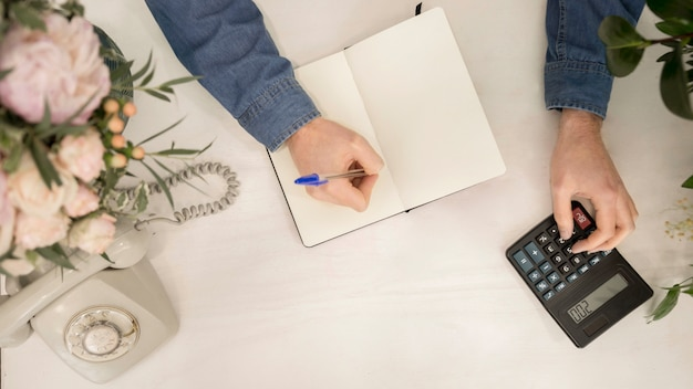 Una vista ambientale di scrittura del fiorista sul taccuino facendo uso del calcolatore sullo scrittorio bianco