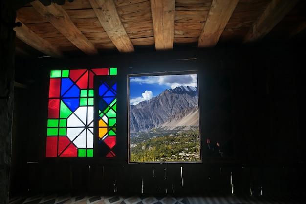 Una vista autunnale della valle di hunza attraverso una finestra nella fortezza di baltit. gilgit baltistan, pakistan.