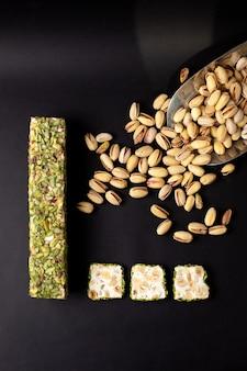 Una vista dall'alto affettato candy bar verde buonissimo insieme alle arachidi sulla scrivania scura