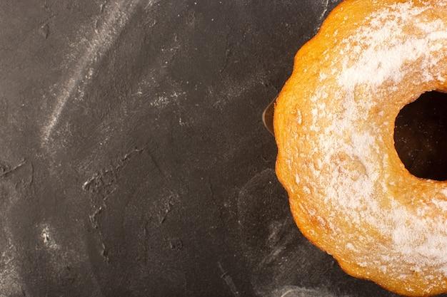 Una vista dall'alto al forno torta rotonda con zucchero in polvere sullo sfondo di legno