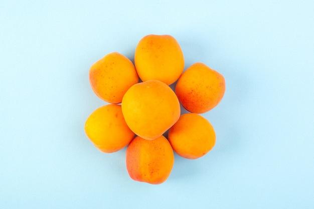 Una vista dall'alto allineato pesche arancioni fresche e mature isolato su sfondo blu ghiaccio frutta vitamina succo