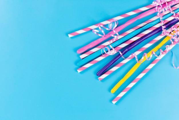 Una vista dall'alto cannucce colorate lunghe appiccicose isolate sul blu, bere succo di colore freddo