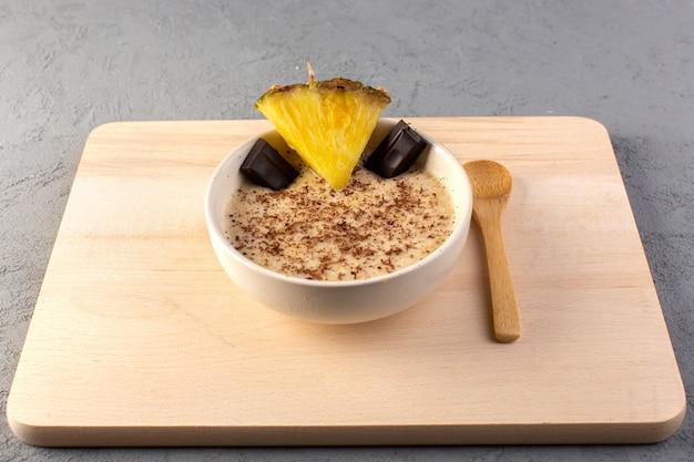 Una vista dall'alto choco dessert marrone con fette di ananas choco bar sulla scrivania in legno color crema e grigio