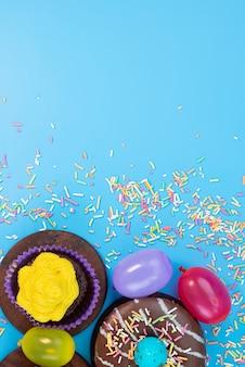 Una vista dall'alto ciambelle e brownies deliziosi ea base di cioccolato insieme a caramelle sul colore blu, torta di caramelle biscotto