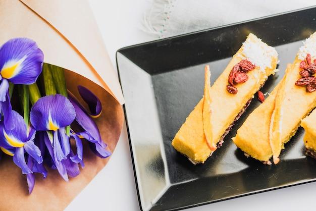 Una vista dall'alto del bouquet di fiori di iris con deliziose fette di torta