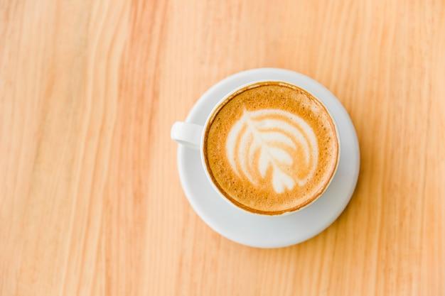 Una vista dall'alto del caffè cappuccino con latte arte sul tavolo di legno