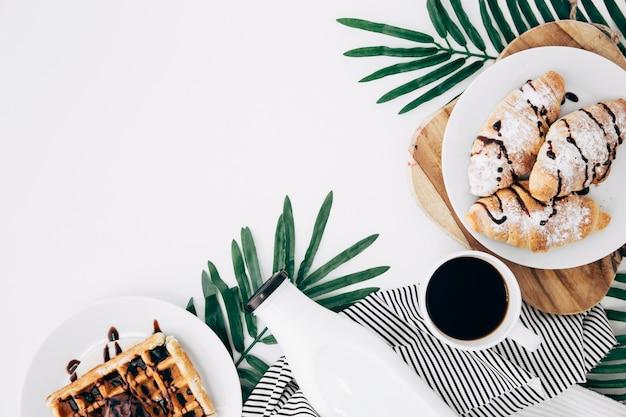 Una vista dall'alto del croissant al forno; cialde; bottiglia; tazza di caffè su foglie sullo sfondo bianco