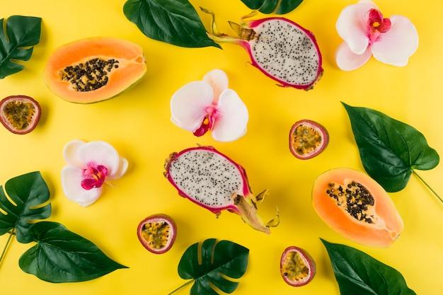Una vista dall'alto del fiore di orchidea; le foglie; frutta del drago e papaia su sfondo giallo