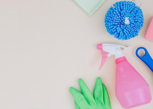 Una vista dall'alto del flacone spray; guanti verdi; spugna su sfondo bianco