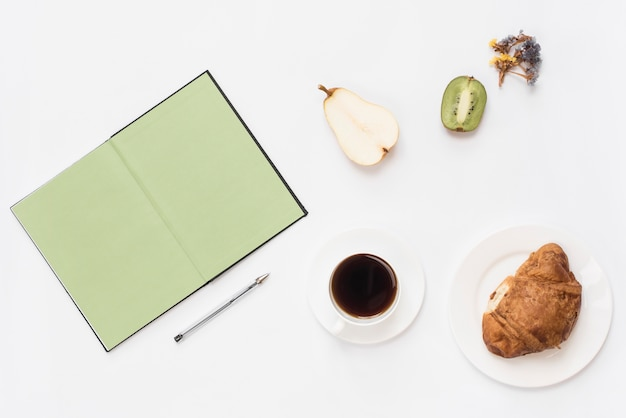 Una vista dall'alto del libro; penna; frutta dimezzata; caffè e croissant su sfondo bianco