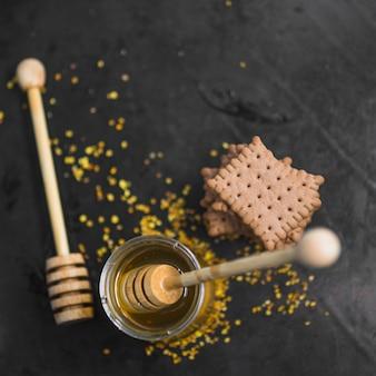 Una vista dall'alto del mestolo di legno nel vaso del miele con pila di biscotti e polline d'api