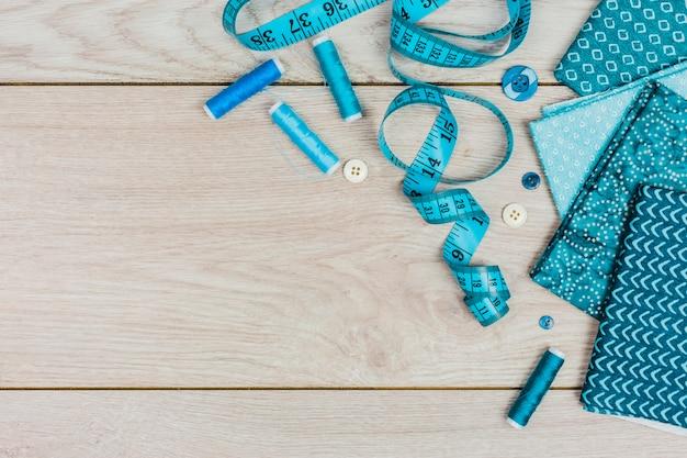Una vista dall'alto del metro a nastro; rocchetti di filo; pulsanti e vestiti piegati sul tavolo di legno