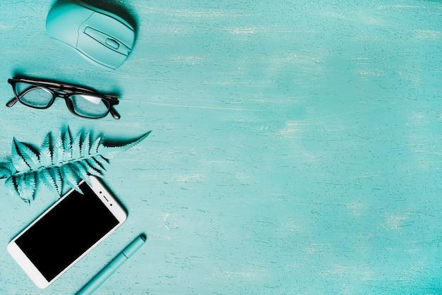 Una vista dall'alto del mouse; occhiali; foglie di felce artificiale; smartphone e penna su sfondo turchese