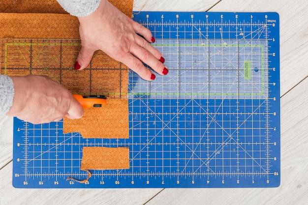 Una vista dall'alto del tessuto di taglio a mano di una donna per la parte più piccola con taglierina rotante sul tavolo di legno