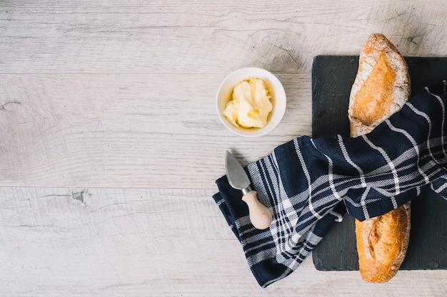 Una vista dall'alto del tovagliolo sopra la baguette al forno; burro; coltello sul fondale in legno bianco