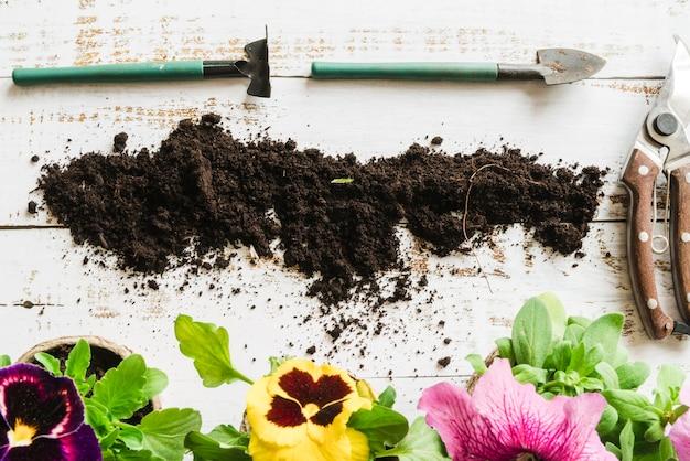 Una vista dall'alto del vaso da fiori giardinaggio con terreno; forbici e attrezzi da giardinaggio sulla scrivania in legno