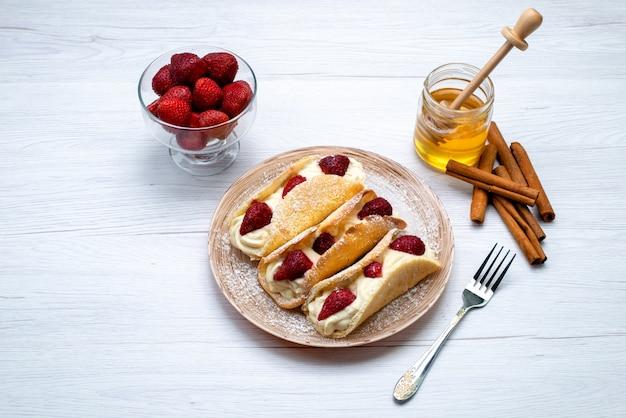 Una vista dall'alto deliziosi bignè con panna e fragole insieme a cannella e miele su sfondo bianco torta di frutta