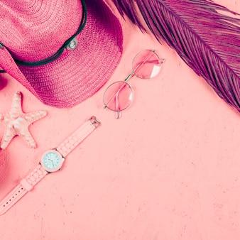 Una vista dall'alto dell'orologio da polso; occhiali da sole; cappello; foglia e stella marina sullo sfondo con texture rosa