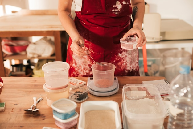 Una vista dall'alto della ceramica femminile che misura la polvere di colore