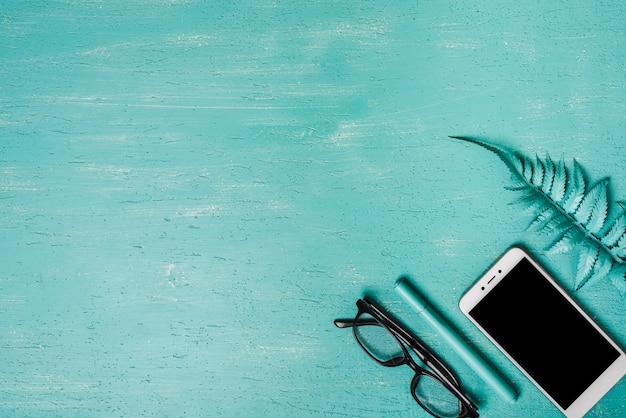 Una vista dall'alto della foglia di felce artificiale; smartphone; penna e occhiali da vista su sfondo turchese