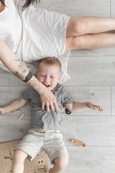 Una vista dall'alto della madre solletico suo figlio sdraiato sul pavimento in legno
