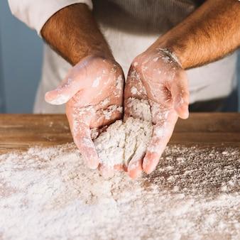 Una vista dall'alto della mano del fornaio con farina di grano