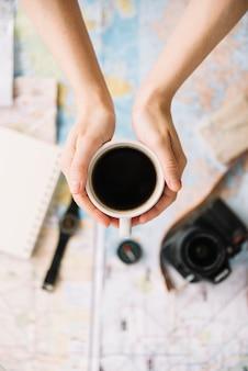 Una vista dall'alto della mano di una persona che tiene tazza di caffè sulla mappa sfocata