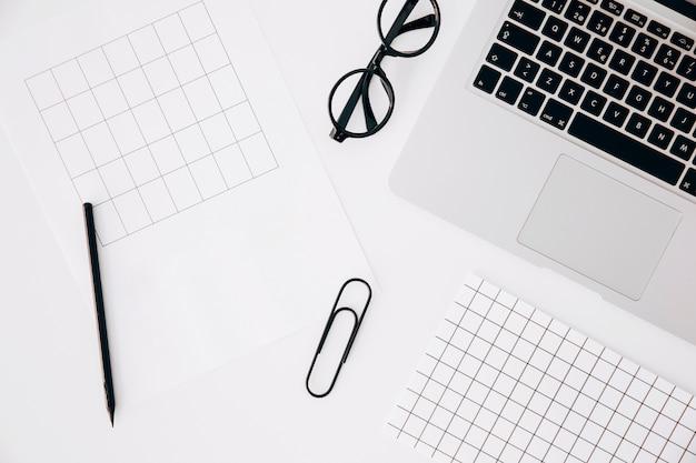 Una vista dall'alto della pagina; matita; graffetta per fogli; occhiali e laptop su sfondo bianco