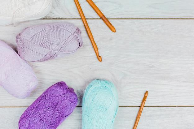 Una vista dall'alto della palla di filato colorato e aghi a maglia sul tavolo di legno