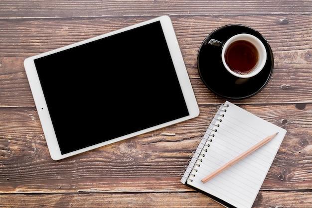 Una vista dall'alto della tavoletta digitale; tazza di caffè e taccuino a spirale con la matita sulla tavola strutturata di legno