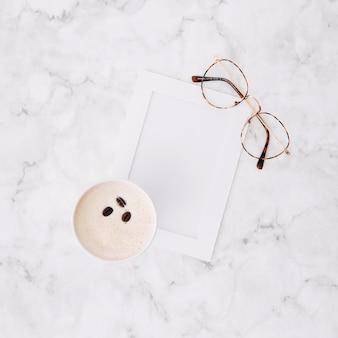 Una vista dall'alto della tazza di caffè usa e getta; cornice vuota e occhiali da vista su marmo con texture di sfondo
