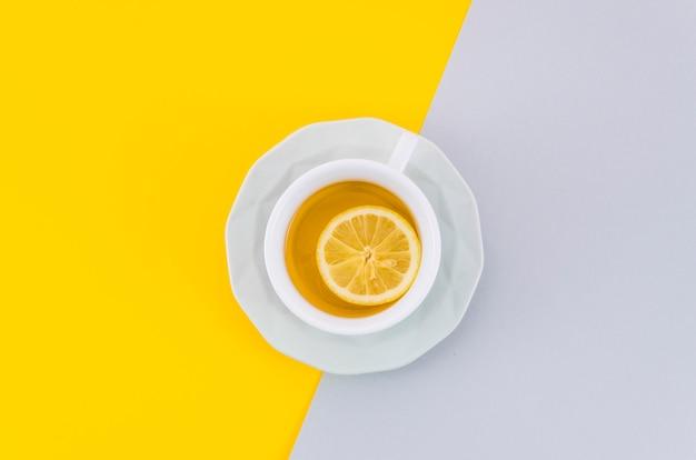 Una vista dall'alto della tazza di tè al limone e piattino su sfondo bianco e giallo