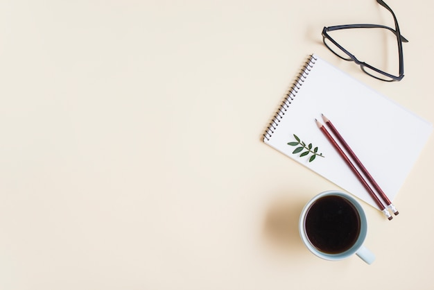 Una vista dall'alto della tazza di tè; occhiali da vista e matita sul blocco note a spirale su sfondo beige