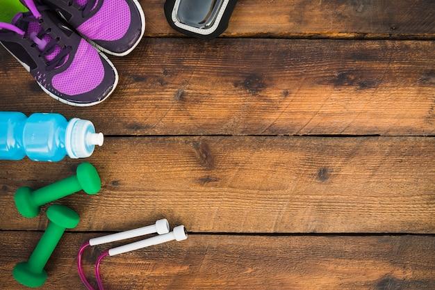 Una vista dall'alto delle scarpe; manubri; corda per saltare; bottiglie d'acqua sul tavolo di legno