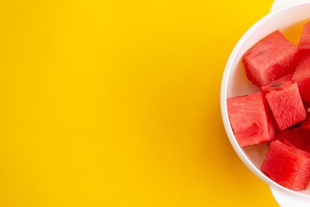 Una vista dall'alto di anguria fresca affettata dolce e pastosa su giallo, frutta color estate
