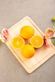 Una vista dall'alto di arance fresche acide mature affettate e agrume intero succosa succosa vitamina tropicale giallo sulla scrivania crema