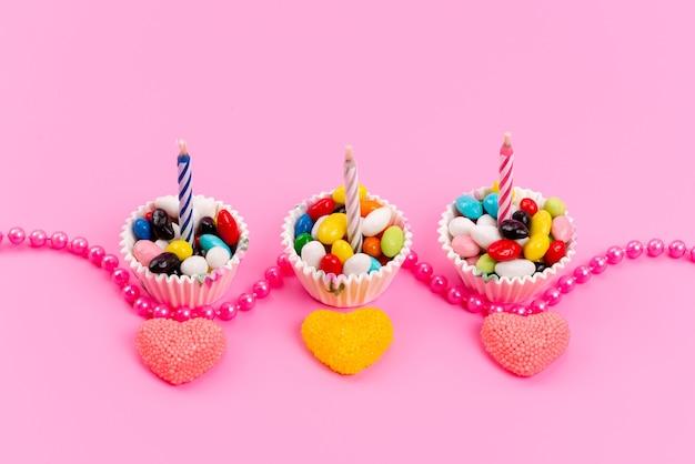 Una vista dall'alto di caramelle multicolori all'interno di pacchetti di carta bianchi insieme a candele e marmellata su dolci di zucchero rosa e arcobaleno di colore