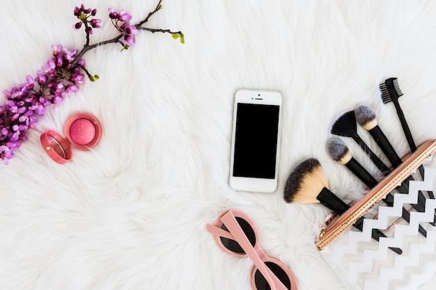 Una vista dall'alto di cipria compatta rosa con occhiali da sole; cellulare; pennello per trucco e ramoscello viola artificiale su pelliccia bianca