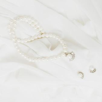 Una vista dall'alto di collana di perle bianche e orecchini su sciarpa bianca