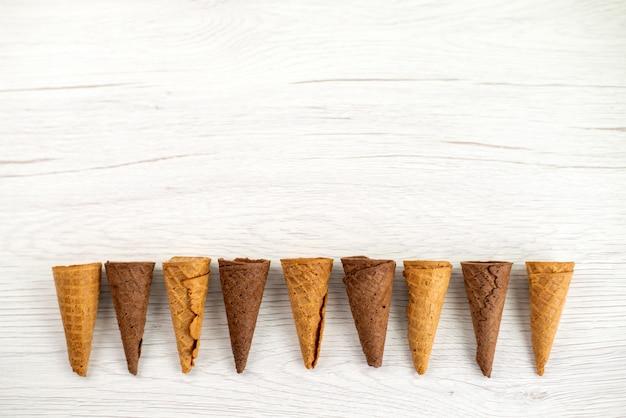 Una vista dall'alto di corna gelato deliziose su caramelle bianche, dessert gelato