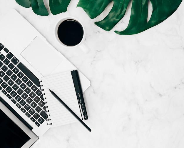 Una vista dall'alto di diario e matita sul laptop; tazza di caffè e foglia di monstera sullo sfondo di marmo