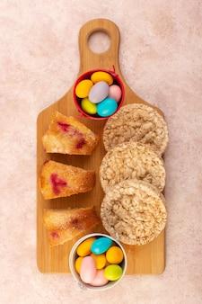 Una vista dall'alto di fette di torta di ciliegie con caramelle e biscotti sul tavolo rosa