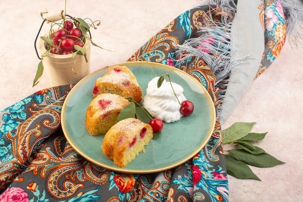 Una vista dall'alto di fette di torta di ciliegie con panna e frutta fresca sullo zucchero rosa biscotto torta da scrivania dolce