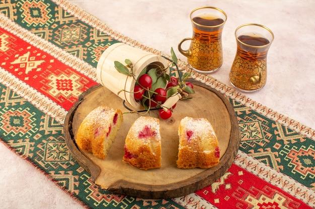 Una vista dall'alto di fette di torta di ciliegie con tè sullo zucchero rosa biscotto torta da scrivania dolce